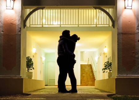 kiss couple: Couple in silhouette Kissing In Front of Apartment Entrance Stock Photo
