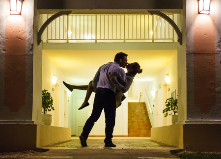 couple lit: Couple in silhouette Kissing In Front of Apartment Entrance Stock Photo