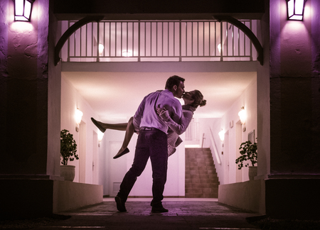 couple lit: Couple Kissing In Front of Apartment Entrance Stock Photo