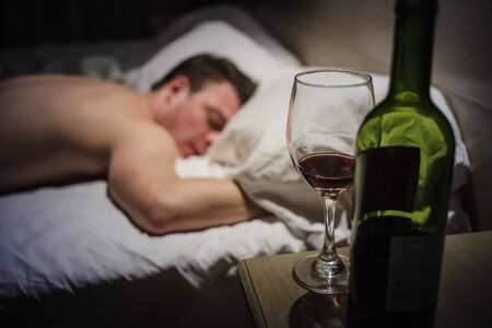 blasted: Hangover Man in a Bed at Night with a Wine Bottle in foreground Stock Photo