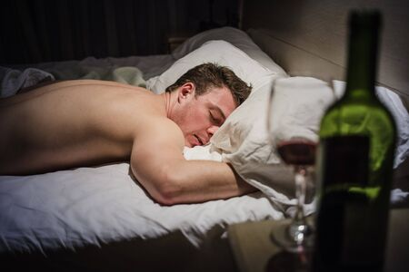 blasted: Hangover Man in a Bed at Night with a Wine Bottle