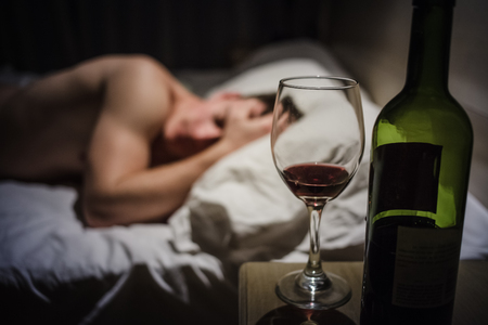 headaches: Hangover Man with Headaches in a Bed at Night and Wine bottle in Focus Stock Photo