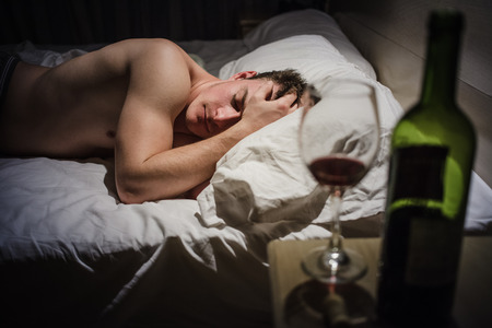 headaches: Hangover Man with Headaches in a Bed at Night and Wine bottle Stock Photo