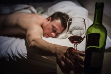 blasted: Lonely Drunk Man Sleeping After a Bottle of Wine. Stock Photo