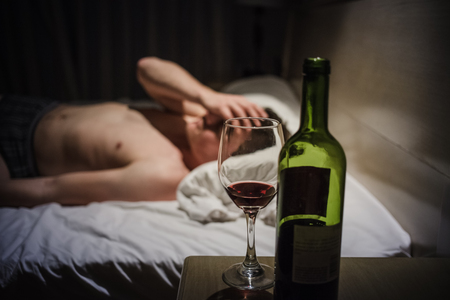 under the influence: Hangover Man with Headaches in a Bed at Night and Wine bottle in Focus Stock Photo
