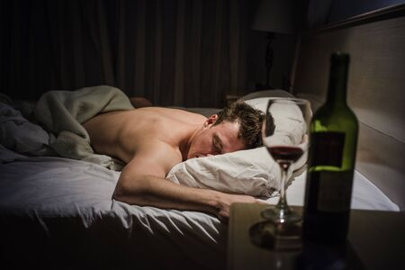 Lonely Drunk Man Sleeping After a Bottle of Wine. Stock Photo