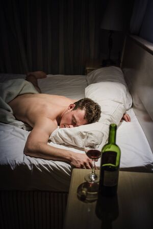 under the influence: Lonely Drunk Man Sleeping After a Bottle of Wine. Stock Photo
