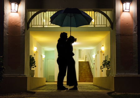 romantic room: Couple in silhouette Kissing Under Umbrella In Front of Apartment Entrance