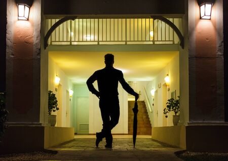 Man in Silhouette with Umbrella Standing up In Front of Apartment Entrance