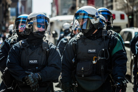 commotion: MONTREAL, CANADA, APRIL 02 2015. Riot in the Montreal Streets to counter the Economic Austerity Measures. Closeup of Cops Portraits Ready in case of Problem
