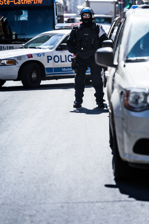 protesters: MONTREAL, CANADA, APRIL 02 2015. Riot in the Montreal Streets to counter the Economic Austerity Measures. Police Alone Watching the Protesters on Ste-Catherine Street Editorial