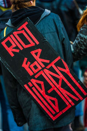 MONTREAL, CANADA, APRIL 02 2015. Riot in the Montreal Streets to counter the Economic Austerity Measures.  Closeup of the Back of a protester Wearing a Sign Saying Riot For Liberty.