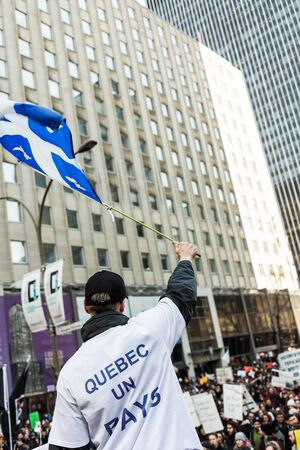 MONTREAL, CANADA, APRIL 02 2015. Riot in the Montreal Streets to counter the Economic Austerity Measures. Separatist Protester Holding the Fleur de Lys Quebec Province Flag