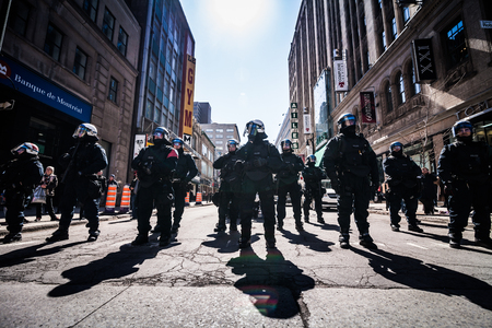 commotion: MONTREAL, CANADA, APRIL 02 2015. Riot in the Montreal Streets to counter the Economic Austerity Measures. Epic Group of Cops Ready to React in case of Problem with Protesters. Editorial