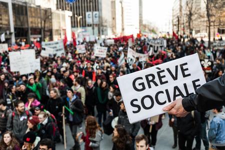 """conflictos sociales: MONTREAL, CANADA, 02 de abril de 2015. Disturbios en las calles de Montreal para contrarrestar las medidas de austeridad econ�mica. Alguien que sostiene un suspiro Decir """"Greve Sociale"""" (franc�s) con borrosa manifestante en antecedentes. Editorial"""