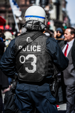 commotion: MONTREAL, CANADA, APRIL 02 2015. Riot in the Montreal Streets to counter the Economic Austerity Measures. Detail of the Back of a Police Facing protesters. Editorial
