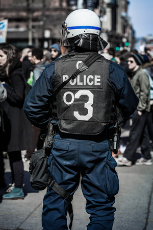 constabulary: MONTREAL, CANADA, APRIL 02 2015. Riot in the Montreal Streets to counter the Economic Austerity Measures. Detail of the Back of a Police Facing protesters. Editorial