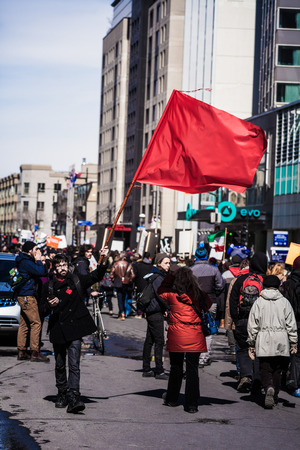 commotion: MONTREAL, CANADA, APRIL 02 2015. Riot in the Montreal Streets to counter the Economic Austerity Measures. Protester Agitating a Red Flag in the Street Editorial