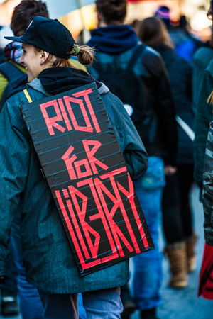 furor: MONTREAL, CANADA, APRIL 02 2015. Riot in the Montreal Streets to counter the Economic Austerity Measures.  Closeup of the Back of a protester Wearing a Sign Saying Riot For Liberty.