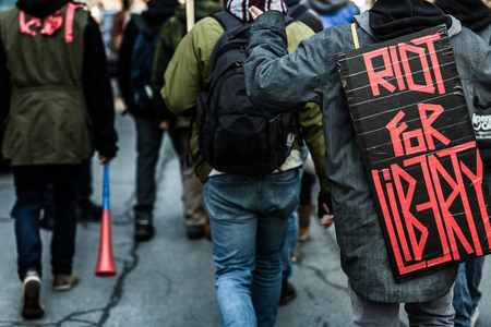 commotion: MONTREAL, CANADA, APRIL 02 2015. Riot in the Montreal Streets to counter the Economic Austerity Measures.  Closeup of the Back of a protester Wearing a Sign Saying Riot For Liberty.