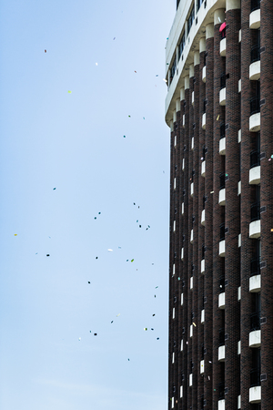 commotion: MONTREAL, CANADA, APRIL 02 2015. Riot in the Montreal Streets to counter the Economic Austerity Measures. Man Throwing Papers from his Balcony to encourage the Protesters Editorial