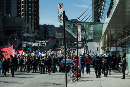 marchers: MONTREAL, CANADA, APRIL 02 2015. Riot in the Montreal Streets to counter the Economic Austerity Measures. Cops Following Marchers in case of something Goes Wrong
