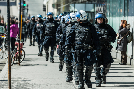 constabulary: MONTREAL, CANADA, APRIL 02 2015. Riot in the Montreal Streets to counter the Economic Austerity Measures.  Cops Following Marchers in case of something Goes Wrong