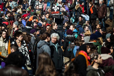 upheaval: MONTREAL, CANADA, APRIL 02 2015. Riot in the Montreal Streets to counter the Economic Austerity Measures. Crowd with Placard, Flags and Signs Walking in the Streets Editorial