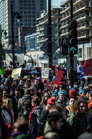 furor: MONTREAL, CANADA, APRIL 02 2015. Riot in the Montreal Streets to counter the Economic Austerity Measures. Crowd with Placard, Flags and Signs Walking in the Streets Editorial