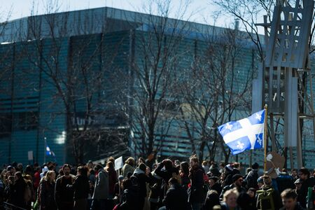 commotion: MONTREAL, CANADA, APRIL 02 2015. Riot in the Montreal Streets to counter the Economic Austerity Measures. Someone Holding Quebec Province Flag in the crowd