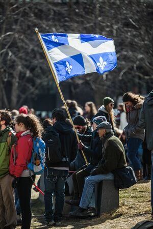 MONTREAL, CANADA, APRIL 02 2015. Riot in the Montreal Streets to counter the Economic Austerity Measures. Someone Holding Quebec Province Flag in the crowd