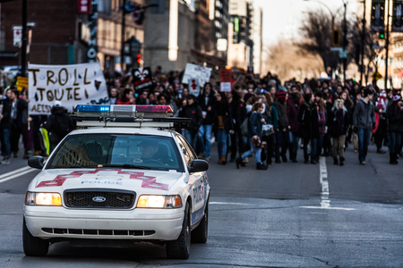 protesters: MONTREAL, CANADA, APRIL 02 2015. Riot in the Montreal Streets to counter the Economic Austerity Measures. Police Car in front of the Protesters controlling the Traffic