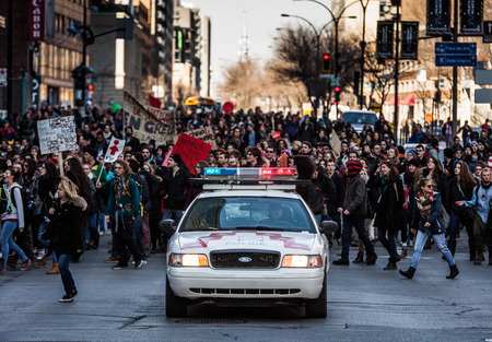 furor: MONTREAL, CANADA, APRIL 02 2015. Riot in the Montreal Streets to counter the Economic Austerity Measures. Police Car in front of the Protesters controlling the Traffic