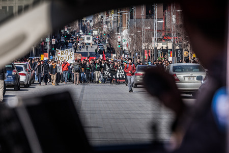 furor: MONTREAL, CANADA, APRIL 02 2015. Riot in the Montreal Streets to counter the Economic Austerity Measures. View of the First line of Protesters walking in the Street Through a Police Car Window