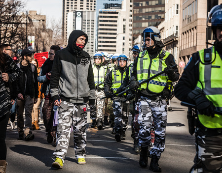 commotion: MONTREAL, CANADA, APRIL 02 2015. Riot in the Montreal Streets to counter the Economic Austerity Measures. Policeman and Protester looking each other in the eyes and wearing the same Army Pants