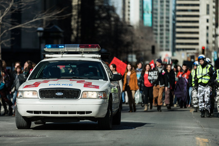 constabulary: MONTREAL, CANADA, APRIL 02 2015. Riot in the Montreal Streets to counter the Economic Austerity Measures. Police Car in front of the Protesters controlling the Traffic