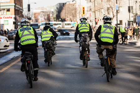 furor: MONTREAL, CANADA, APRIL 02 2015. Riot in the Montreal Streets to counter the Economic Austerity Measures. Four Cops using Bike for Fast and easy Moving.