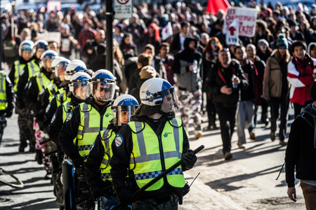 upheaval: MONTREAL, CANADA, APRIL 02 2015. Riot in the Montreal Streets to counter the Economic Austerity Measures. Cops Following the Marchers to make sure everything is under Control