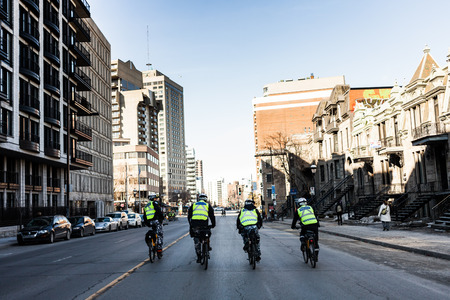 authorities: MONTREAL, CANADA, APRIL 02 2015. Riot in the Montreal Streets to counter the Economic Austerity Measures. Four Cops using Bike for Fast and easy Moving.