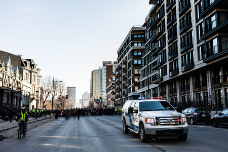 austerity: MONTREAL, CANADA, APRIL 02 2015. Riot in the Montreal Streets to counter the Economic Austerity Measures. Police Pick-up Truck in front of the Protesters controlling the Traffic