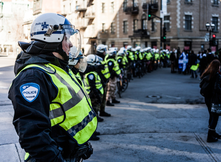 austerity: MONTREAL, CANADA, APRIL 02 2015. Riot in the Montreal Streets to counter the Economic Austerity Measures. Cops making a line to Control the Protesters