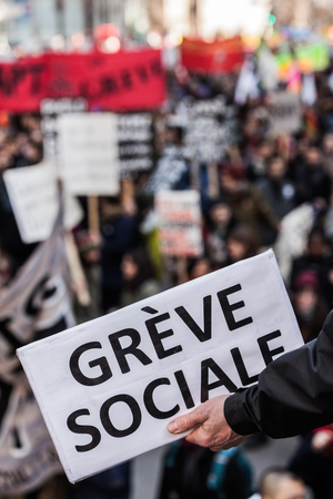 furor: MONTREAL, CANADA, APRIL 02 2015. Riot in the Montreal Streets to counter the Economic Austerity Measures. Someone Holding a Sigh Saying Greve Sociale (French) with Blurry Protester in Background. Editorial