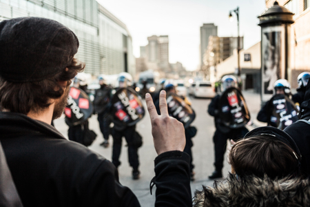 furor: MONTREAL, CANADA, APRIL 02 2015. Riot in the Montreal Streets to counter the Economic Austerity Measures. Man making a Peace sign in front of cops