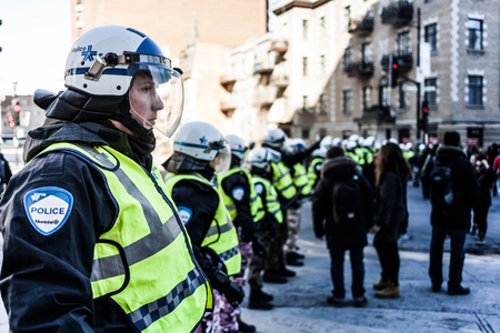 furor: MONTREAL, CANADA, APRIL 02 2015. Riot in the Montreal Streets to counter the Economic Austerity Measures. Cops making a line to Control the Protesters