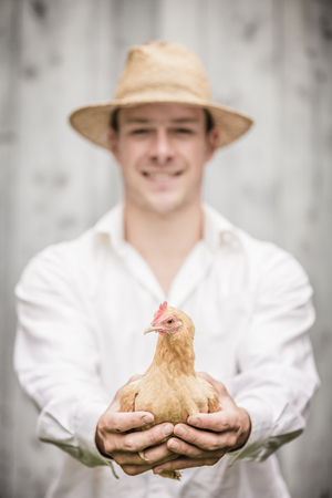 agronomist: Farmer Holding a Beige Chicken in front of the Farm