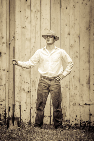 agronomist: Young Proud Farmer standing up in front of Barn