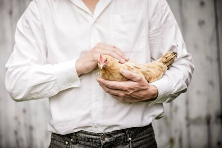 Farmer Holding a Beige Chicken in front of the Farm