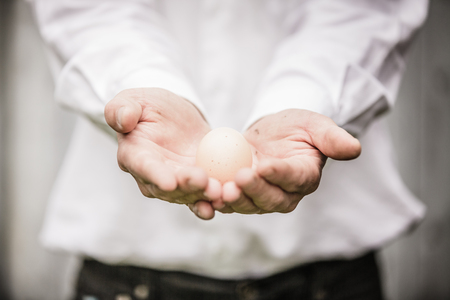 Farmer Showing an Egg in front of the Farm