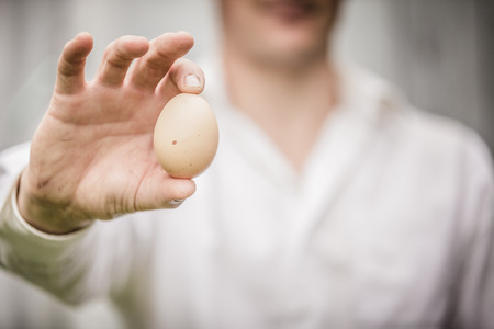 agronomist: Farmer Showing an Egg in front of the Farm