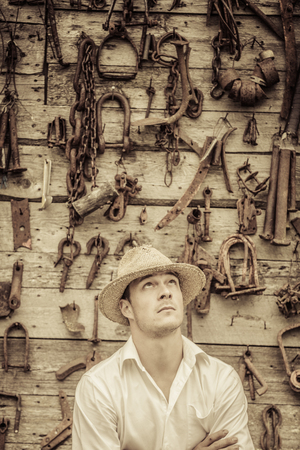 Farmer Portrait in front of a Wall Full with Old Rusty Tools Stock Photo